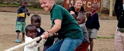 Childcare volunteer plays a game with children during her work experience in Ghana.